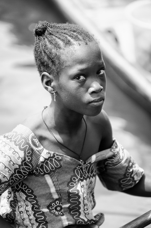 PORTO-NOVO, BENIN - MAR 9, 2012: Unidentified Beninese woman in a wooden boat. People of Benin suffer of poverty due to the difficult economic situation. Editorial