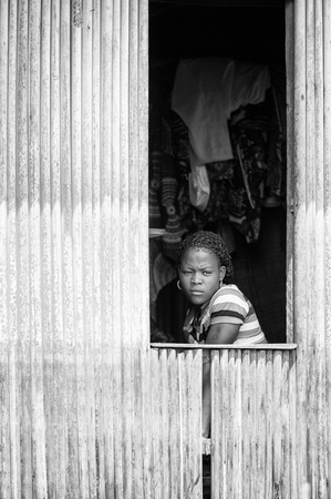 third age: PORTO-NOVO, BENIN - MAR 9, 2012: Unidentified Beninese girl looks out of the window. People of Benin suffer of poverty due to the difficult economic situation