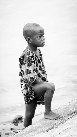 third age: PORTO-NOVO, BENIN - MAR 9, 2012: Unidentified Beninese angry boy comes out of the water. Children of Benin suffer of poverty due to the difficult economic situation