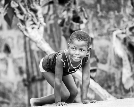 PORTO-NOVO, BENIN - MAR 9, 2012: Unidentified Beninese little girl plays outdoor. Children of Benin suffer of poverty due to the difficult economic situation