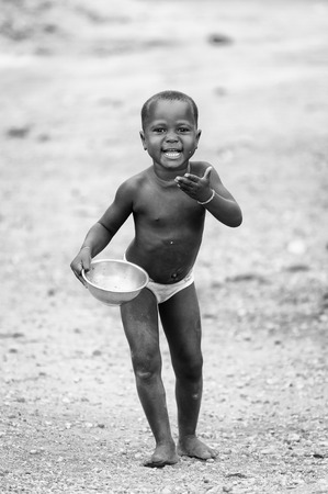 third eye: PORTO-NOVO, BENIN - MAR 9, 2012: Unidentified Beninese little boy with an empty plate outdoor. Children of Benin suffer of poverty due to the difficult economic situation Editorial