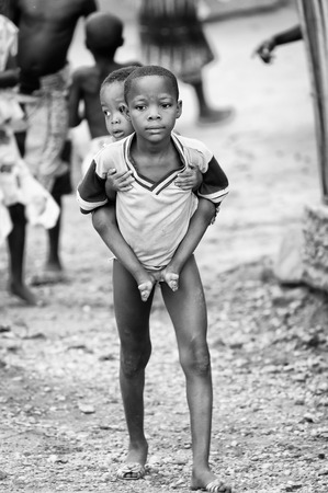 third eye: PORTO-NOVO, BENIN - MAR 10, 2012: Unidentified Beninese lboy carries his little brother in the street. People of Benin suffer of poverty due to the difficult economic situation