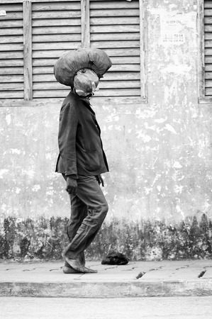 PORTO-NOVO, BENIN - MAR 10, 2012: Unidentified Beninese man walks with a stuff on his head. People of Benin suffer of poverty due to the difficult economic situation