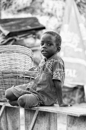 PORTO-NOVO, BENIN - MAR 10, 2012: Unidentified Beninese boy walks on the wooden bench. People of Benin suffer of poverty due to the difficult economic situation Editorial