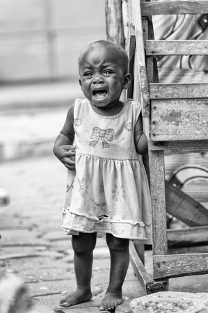 PORTO-NOVO, BENIN - MAR 10, 2012: Unidentified Beninese little girl in a blue dress cries loudly. People of Benin suffer of poverty due to the difficult economic situation