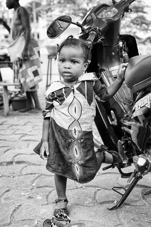 Porto-Novo, Benin - MAR 10, 2012: non identificato bambina Benin con le trecce in un abito viola nei pressi di moto. La gente del Benin soffrono di povertà a causa della difficile situazione economica