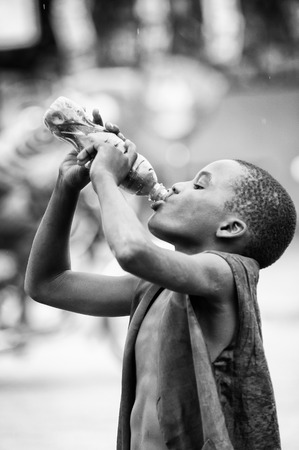 third age: PORTO-NOVO, BENIN - MAR 10, 2012: Unidentified Beninese boy drinks a juice from a bottle. People of Benin suffer of poverty due to the difficult economic situation