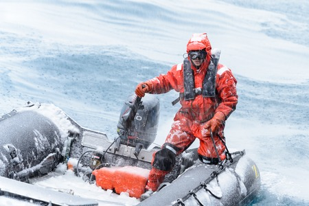 SOUTH GEORGIA, GREAT BRITAIN - NOV 9, 2012:  Unidentified man in a water proof suite in a rubber boat with a motor in the Atlantic Ocean. Atlantic Ocean is the worlds second largest ocean