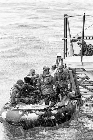 lifevest: SOUTH GEORGIA, GREAT BRITAIN - NOV 9, 2012: Unidentified group of people in a water proof suit in a rubber boat with a motor in the Atlantic Ocean. Atlantic Ocean is the worlds second largest ocean