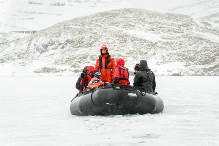 lifevest: SOUTH GEORGIA, GREAT BRITAIN - NOV 9, 2012: Unidentified group of people and a child in a water proof suit in a rubber boat in the Atlantic Ocean. Atlantic Ocean is the worlds second largest ocean