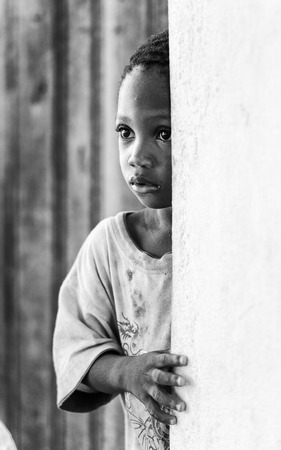 ploblem: KARA, TOGO - MAR 9, 2013: Unidentified Togolese girl near a wall of a house. Children in Togo suffer of poverty due to the unstable econimic situation Editorial