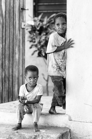 ploblem: KARA, TOGO - MAR 9, 2013: Unidentified Togolese boy sits at the porch of a house. Children in Togo suffer of poverty due to the unstable econimic situation