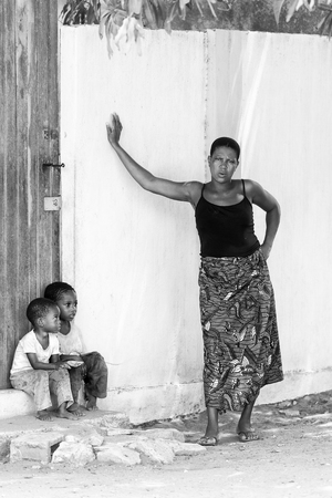 ploblem: KARA, TOGO - MAR 9, 2013: Unidentified Togolese children sit near a house door. Children in Togo suffer of poverty due to the unstable econimic situation Editorial