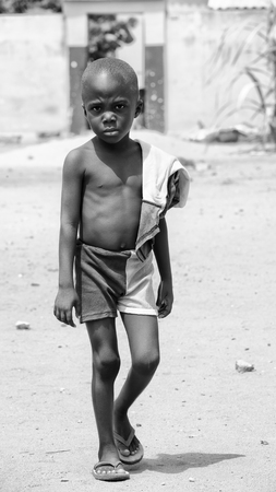 ploblem: KARA, TOGO - MAR 9, 2013: Unidentified Togolese boy with sad eyes walks in the street. Children in Togo suffer of poverty due to the unstable econimic situation