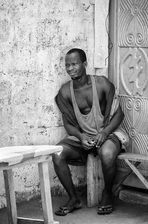 ploblem: KARA, TOGO - MAR 9, 2013: Unidentified Togolese man sits on a bench. People in Togo suffer of poverty due to the unstable econimic situation