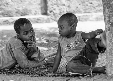 ploblem: KARA, TOGO - MAR 9, 2013: Unidentified Togolese boys sit near a tree. Children in Togo suffer of poverty due to the unstable econimic situation