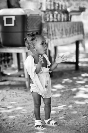 ploblem: KARA, TOGO - MAR 9, 2013: Unidentified Togolese girl claps her hands in the street. Children in Togo suffer of poverty due to the unstable econimic situation