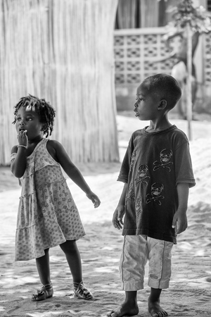 ploblem: KARA, TOGO - MAR 9, 2013: Unidentified Togolese boy and girl playing in the street. Children in Togo suffer of poverty due to the unstable econimic situation