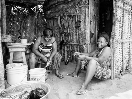 ploblem: KARA, TOGO - MAR 9, 2013: Unidentified Togolese women sit near their  house. People in Togo suffer of poverty due to the unstable econimic situation Editorial