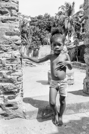 ploblem: KARA, TOGO - MAR 9, 2013: Unidentified Togolese girl runs in the street. Children in Togo suffer of poverty due to the unstable econimic situation Editorial