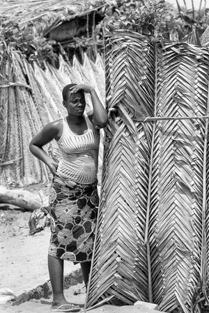 ploblem: KARA, TOGO - MAR 9, 2013: Unidentified Togolese woman stays near a house. People in Togo suffer of poverty due to the unstable econimic situation