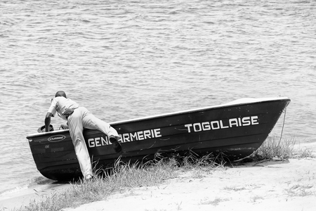 ploblem: KARA, TOGO - MAR 9, 2013: Unidentified Togolese policeman check out a boat. People in Togo suffer of poverty due to the unstable econimic situation