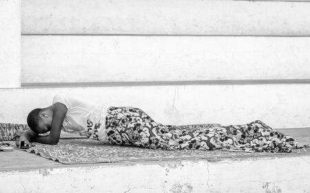 ploblem: KARA, TOGO - MAR 9, 2013: Unidentified Togolese woman lays near a house. People in Togo suffer of poverty due to the unstable econimic situation
