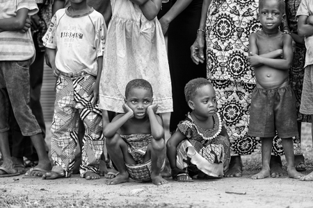 ploblem: KARA, TOGO - MAR 9, 2013: Unidentified Togoles girls watch a local show. People in Togo suffer of poverty due to the unstable econimic situation