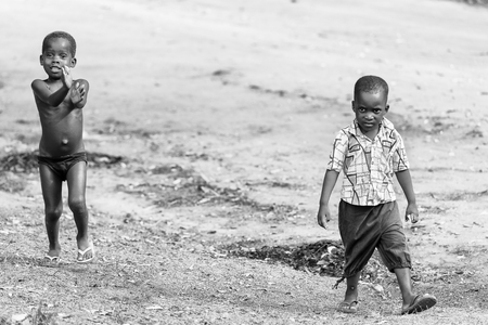 ploblem: KARA, TOGO - MAR 9, 2013: Unidentified Togolese children run and play in the street. Children in Togo suffer of poverty due to the unstable econimic situation