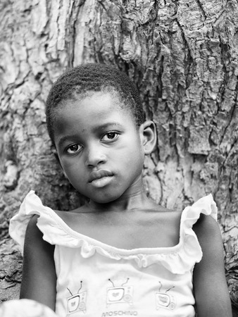 ploblem: KARA, TOGO - MAR 9, 2013: Unidentified Togolese girl sits near a tree. Children in Togo suffer of poverty due to the unstable econimic situation Editorial