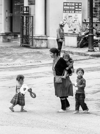 sapa: SAPA, VIETMAN - SEP 22, 2014: Unidentified Hmong woman in a traditional dress and her children in Sapa, Vietnam. Hmong is a minority ethnic group of Vietnam Editorial