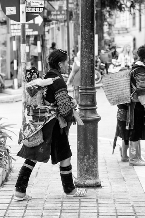 sapa: SAPA, VIETMAN - SEP 22, 2014: Unidentified Hmong woman in a traditional dress carries her little baby on her back in Sapa, Vietnam. Hmong is a minority ethnic group of Vietnam