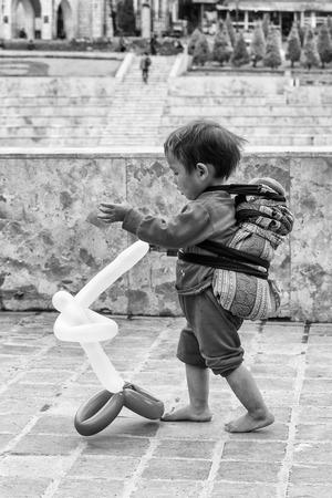 sapa: SAPA, VIETMAN - SEP 22, 2014: Unidentified Hmong boy plays with an air baloon in Sapa, Vietnam. Hmong is a minority ethnic group of Vietnam