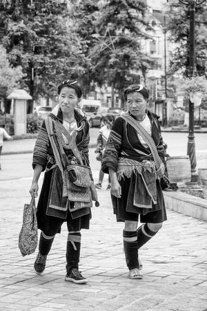 sapa: SAPA, VIETMAN - SEP 22, 2014: Unidentified Hmong women in a traditional dress walking down the street in Sapa, Vietnam. Hmong is a minority ethnic group of Vietnam