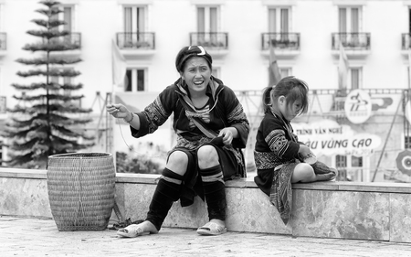 sapa: SAPA, VIETMAN - SEP 22, 2014: Unidentified Hmong woman and her daughter are sewing in the street in Sapa, Vietnam. Hmong is a minority ethnic group of Vietnam Editorial