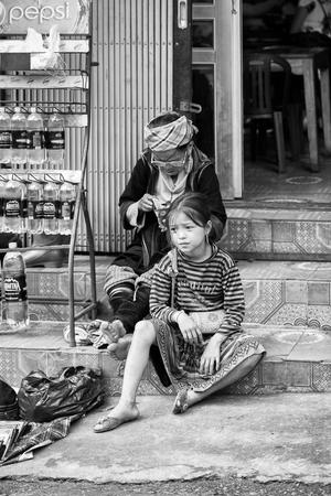 sapa: SAPA, VIETMAN - SEP 22, 2014: Unidentified Hmong girl sits on the ground  in Sapa, Vietnam. Hmong is a minority ethnic group of Vietnam