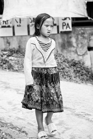 sapa: SAPA, VIETMAN - SEP 22, 2014: Unidentified Hmong girl walks in the street in Sapa, Vietnam. Hmong is a minority ethnic group of Vietnam