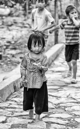 vietnamese ethnicity: CATCAT VILLAGE, VIETMAN - SEP 12, 2014: Unidentified Vietnamese girl eats a candy in the Catcat village, Vietnam. 86 of Vietnamese people belong to the Viet ethnic group