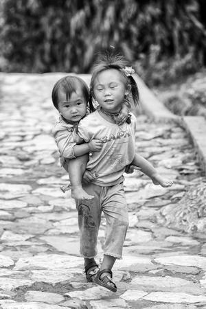 vietnamese ethnicity: CATCAT VILLAGE, VIETMAN - SEP 12, 2014: Unidentified Vietnamese beautiful girl carries her sister in the Catcat village, Vietnam. 86 of Vietnamese people belong to the Viet ethnic group