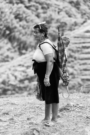 SAPA, VIETMAN - SEP 22, 2014: Unidentified Hmong woman with her baby on her back in Sapa, Vietnam. Hmong is a minority ethnic group of Vietnam