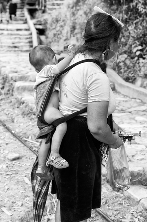 sapa: SAPA, VIETMAN - SEP 22, 2014: Unidentified Hmong woman with her baby on her back in Sapa, Vietnam. Hmong is a minority ethnic group of Vietnam