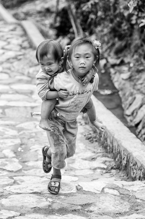 CATCAT VILLAGE, VIETMAN - SEP 12, 2014: Unidentified Vietnamese beautiful girl carries her sister in the Catcat village, Vietnam. 86 of Vietnamese people belong to the Viet ethnic group