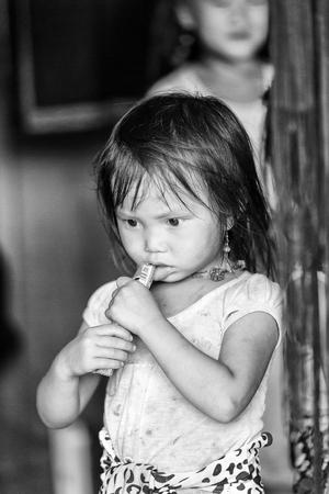 CATCAT VILLAGE, VIETMAN - SEP 12, 2014: Unidentified Vietnamese girl eats a candy in the Catcat village, Vietnam. 86 of Vietnamese people belong to the Viet ethnic group