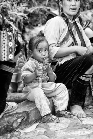 sapa: SAPA, VIETMAN - SEP 22, 2014: Unidentified Hmong girl with a candy in Sapa, Vietnam. Hmong is a minority ethnic group of Vietnam