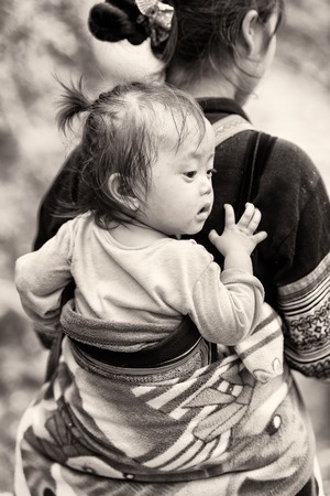 CATCAT VILLAGE, VIETMAN - SEP 12, 2014: Unidentified Vietnamese girl on her mother back in the Catcat village, Vietnam. 86 of Vietnamese people belong to the Viet ethnic group
