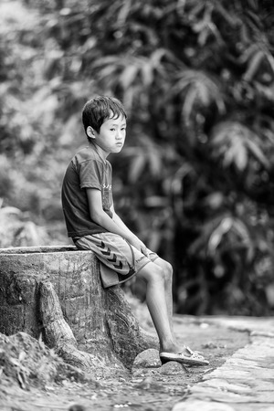 SAPA, VIETMAN - SEP 22, 2014: Unidentified Hmong boy sits and thinks in Sapa, Vietnam. Hmong is a minority ethnic group of Vietnam