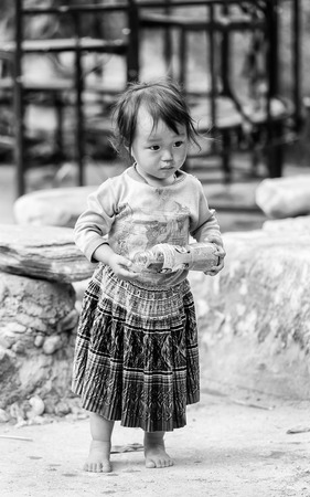 CATCAT VILLAGE, VIETMAN - SEP 12, 2014: Unidentified Vietnamese beautiful girl with an empty bottle in the Catcat village, Vietnam. 86 of Vietnamese people belong to the Viet ethnic group