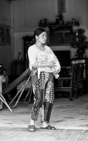 sapa: SAPA, VIETMAN - SEP 22, 2014: Unidentified Hmong woman with her baby on arms drinking brest milk in Sapa, Vietnam. Hmong is a minority ethnic group of Vietnam