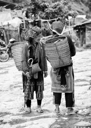sapa: SAPA, VIETMAN - SEP 22, 2014: Unidentified Hmong women a traditional dresses with buckets on their back in Sapa, Vietnam. Hmong is a minority ethnic group of Vietnam Editorial