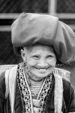 sapa: SAPA, VIETMAN - SEP 22, 2014: Unidentified Hmong woman in a traditional dress smiles with teethless mouth in Sapa, Vietnam. Hmong is a minority ethnic group of Vietnam